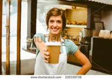 stock-photo-pretty-barista-smiling-at-camera-holding-disposable-cup-at-the-coffee-shop-220330738