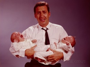 h-armstrong-roberts-distressed-looking-father-holding-crying-twin-babies-in-his-arms